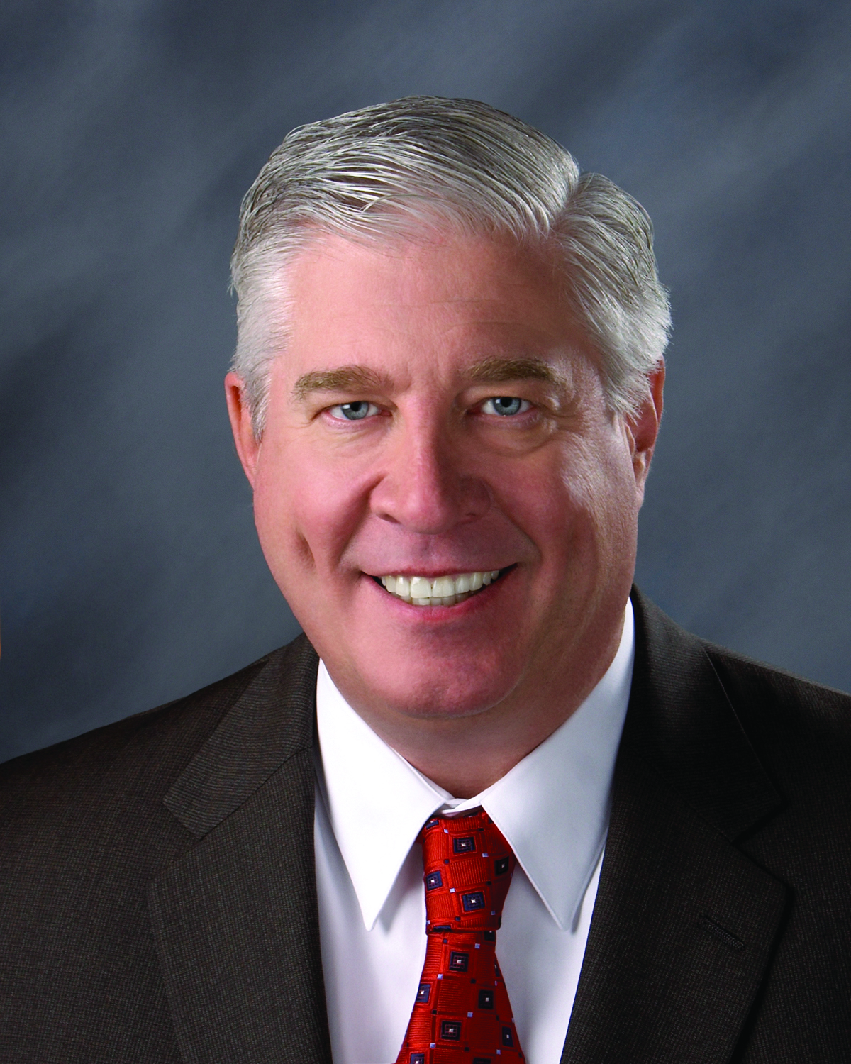 Jim Emme, an older, light-skin, male-presenting person with gray hair and blue eyes in a suit with a red tie smiles at the camera.