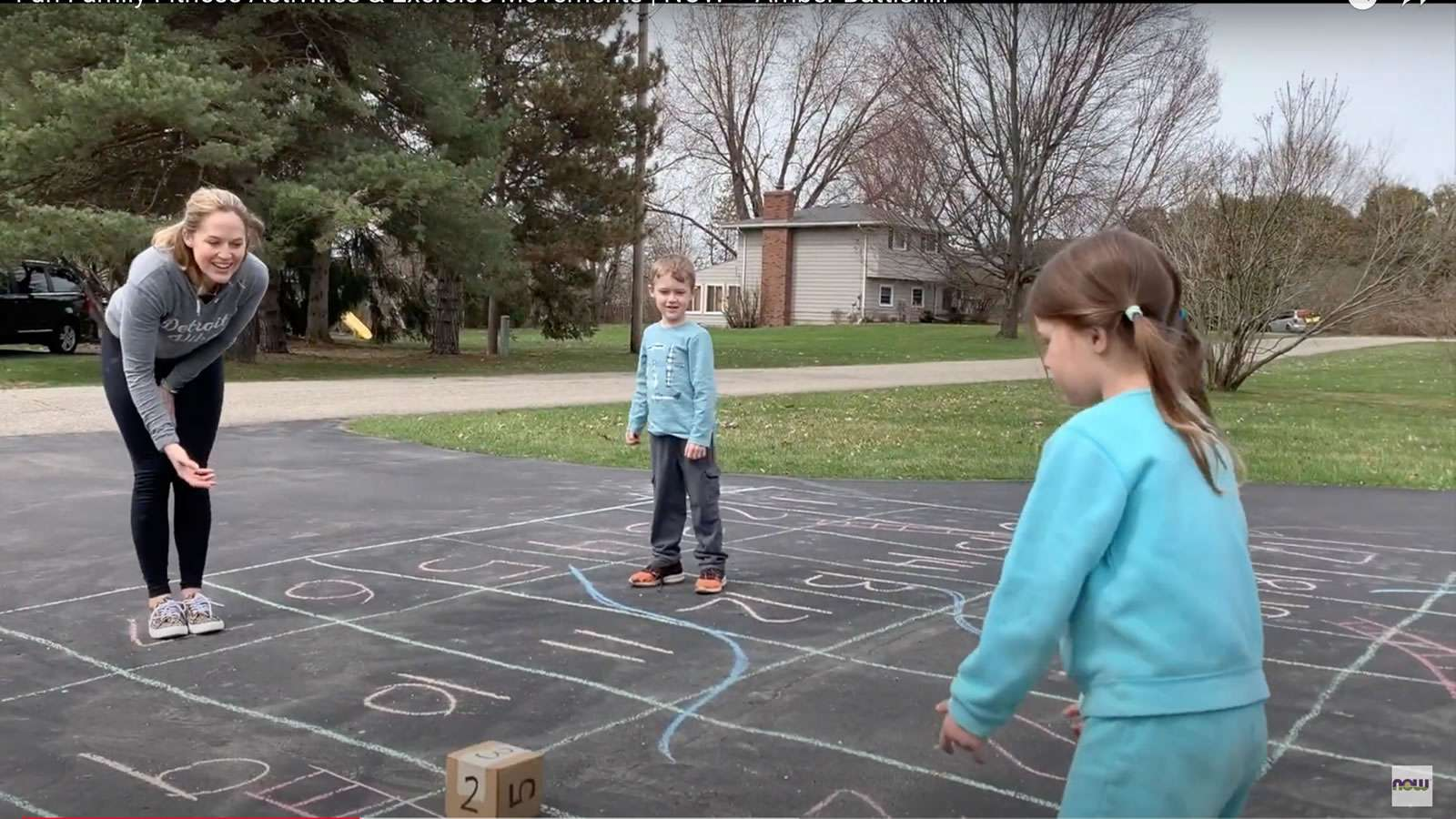 boy and girl playing chalk game on driveway with mom