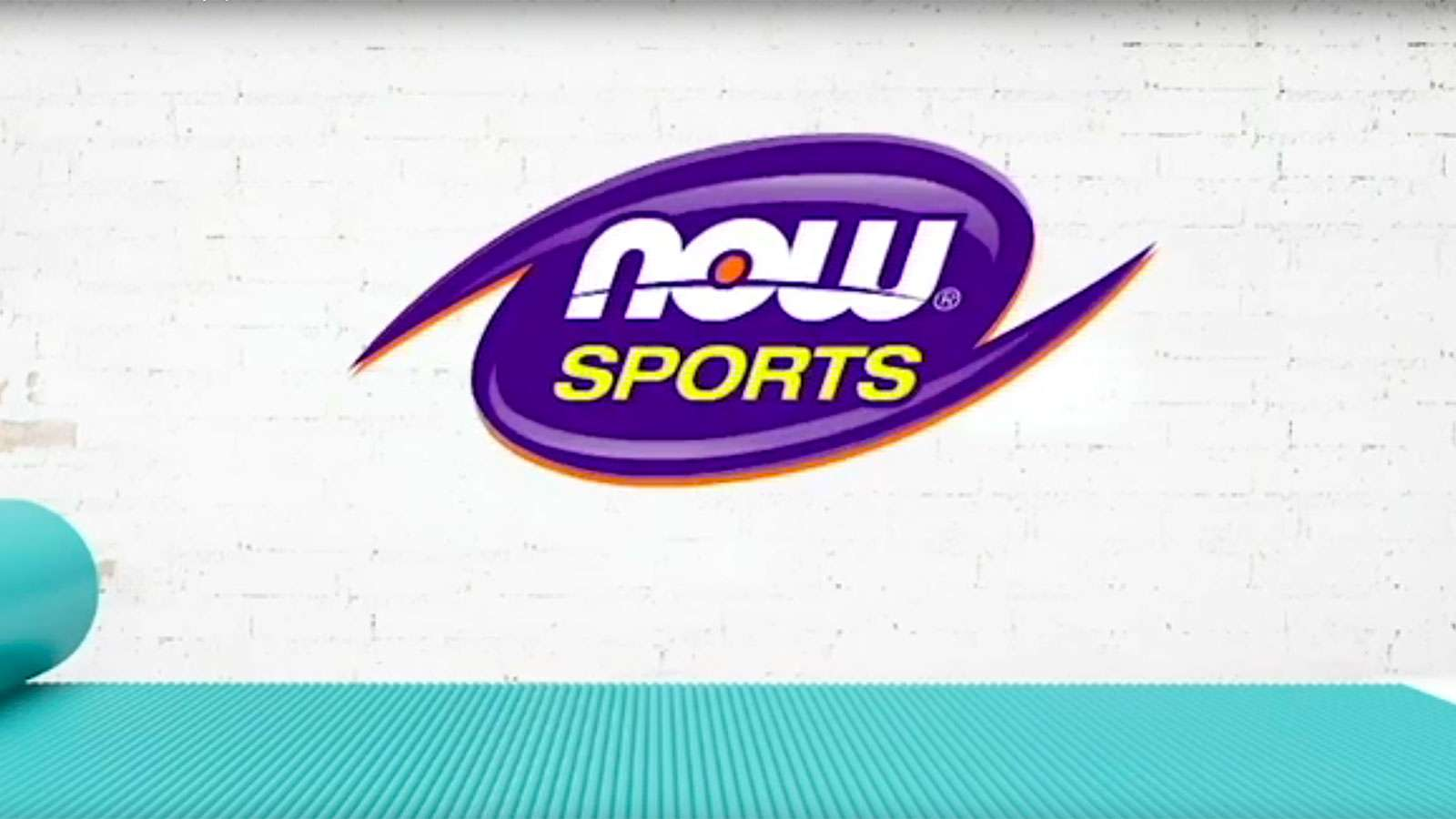 The logo for NOW Sports against a white brick wall. A light blue yoga mat is laid out on the floor.