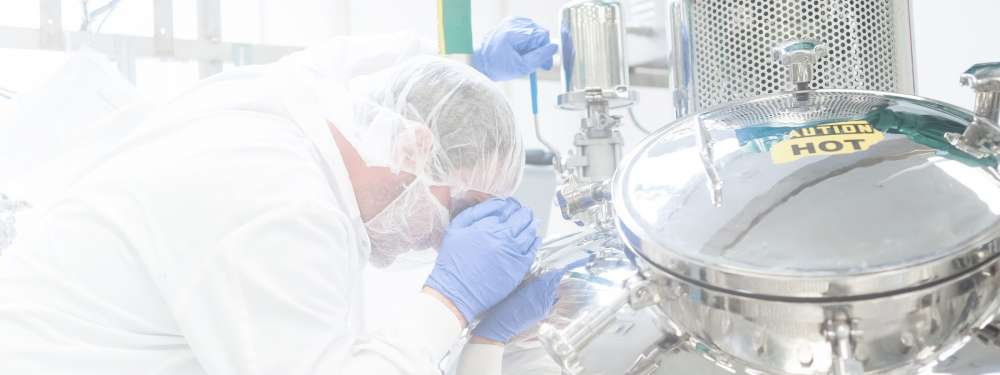An employee in a lab coat wearing a hairnet, facemask, and gloves looks inside a metallic machine.