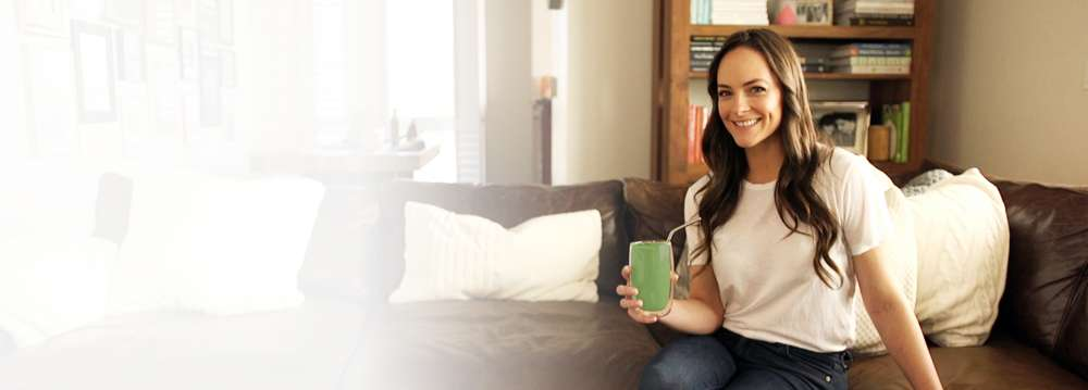 Kelly LeVeque sitting with a green BodyLoveNOW50 smoothie image