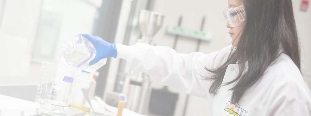 A female-presenting scientist in a lab pours liquid into a beaker